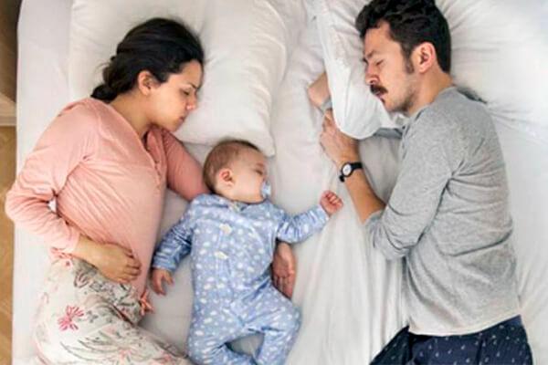 niño en colecho para dormir en la cama con los padres